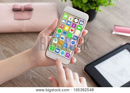 female hands holding white phone with home screen icons apps and e-rider
