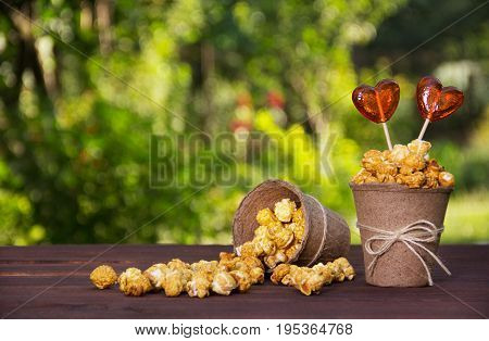 A paper bucket with caramelized popcorn and lollipops on a green natural background. A bucket with scattered popcorn.