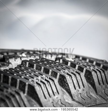 Tread winter car tire with spikes close-up.