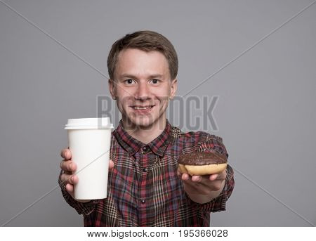Young man holding glaced donut and paper cup isolated on grey background