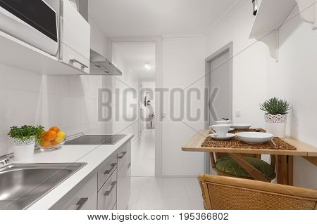 A Brightly Lit Clean White Kitchen With a Set Table