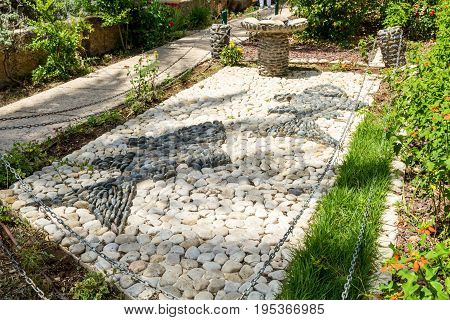 SEA OF GALILEE ISRAEL - MAY 15: Stone sculpture composition - two fish and five loaves of bread in landscape park Church of Mount of Beatitudes at the Sea of Galilee Israel on May 15 2017