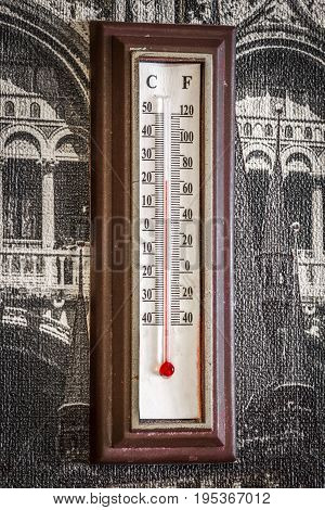 Old mercury wall room thermometer close up.