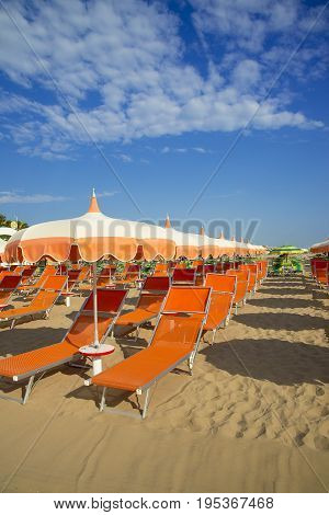Orange umbrellas and chaise lounges on the beach of Rimini in Italy - the destination in the Adriatic coast of Emilia-Romagna