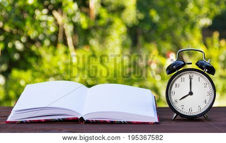Open book with white pages and clocks. Black alarm clock and a notebook. Copy space