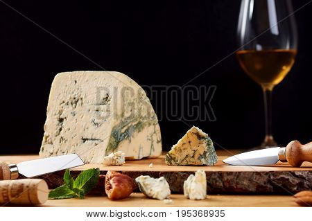 Slice of French Roquefort cheese with mint. Blue cheese in wooden board. Cheese with glass of wine.