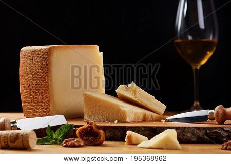 Close-up of a Parmesan cheese with glass of wine. Cheese on wooden board