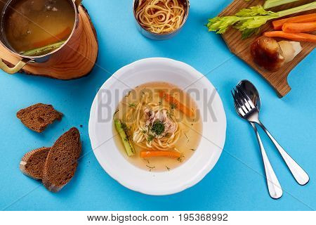 Chicken broth with mushroom noodles and vegetables. Light soup on a blue background. Top view
