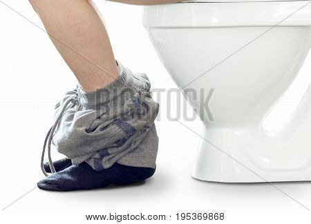 The man is sitting on the toilet bowl close-up on a white background.