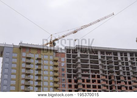 Yellow Construction Tower Crane Against Gray Cloudy Sky
