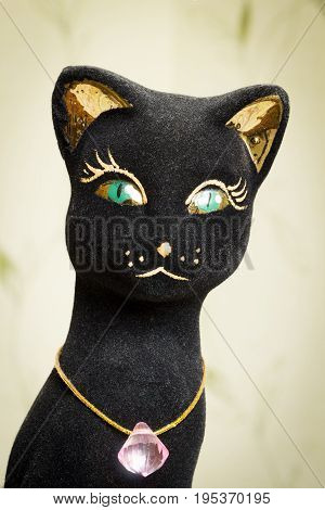 A statuette of a black cat with a jewel on the neck.
