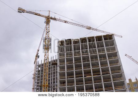 Construction work site and high rise crane building Against the gray sky