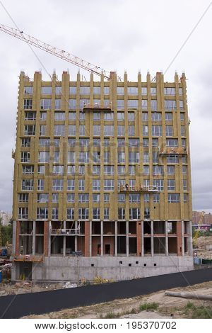 Highlanders insulate the high-rise building of the mineral cotton Against the gray sky