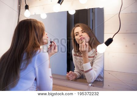 beautiful girl stands before the mirror and makes makeup 1