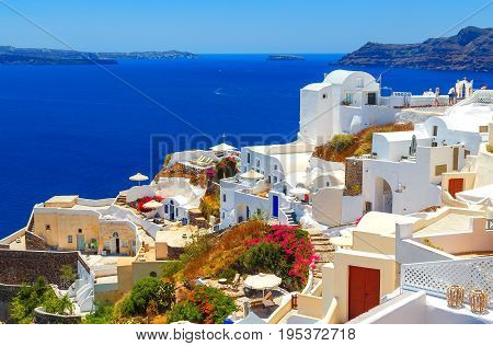 Oia town on Santorini island, Greece. Traditional and famous houses and churches with blue domes over Caldera, Aegean sea