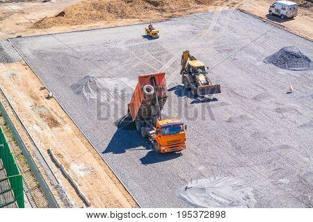 Dump truck unloads asphalt at the construction site of the school stadium.