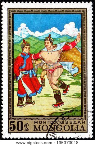 UKRAINE - CIRCA 2017: A postage stamp printed in Mongolia shows Athletes Two men dance from the series Paintings by contemporary artists in Ulan Bator Museum circa 1972