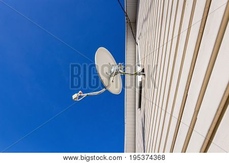 Satellite dish mounted on the wall of a private house