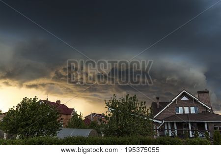 Summer black storm clouds over the village.