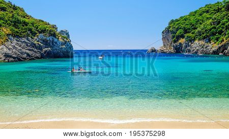 CORFU, GREECE - JULY 5, 2017:  View on the beach Paleokastritsa with unknown tourists paddling.