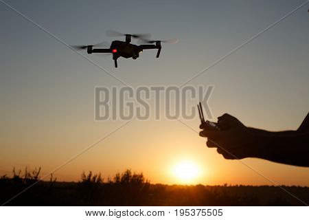 Man holds remote controller with his hands while copter is flying on background. Drone hovers behind the pilot on suset.