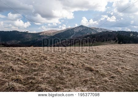 panorama of spring Velka Fatra mountains near Chyzky guidepost in Liptov region in Slovakia with mountain meadow hills with small snow fields and blue sky with clouds