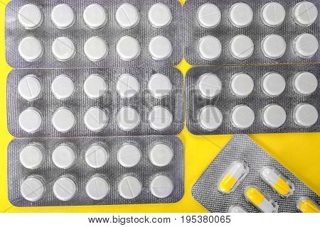 A top view of saturated gray packs with round white tablets on a shiny yellow background. Aspirin and painkillers in colorful capsules. Recovery, healing, therapy concept.