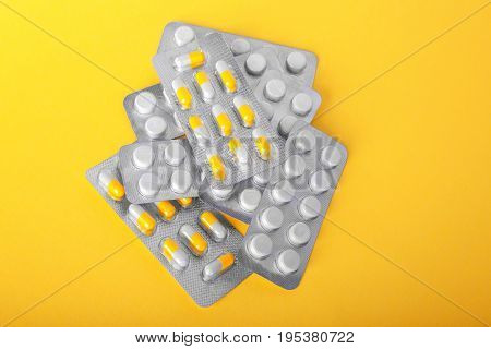 Shiny blisters with colorful white and yellow pills on a tellow background. Prescripted drugs in capsules. Antibiotics and painkillers in tablets. Medical treatment and pharmaceutical therapy.