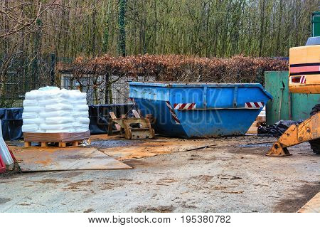 Blue container an excavator and pallet with white bags on a construction site in the forest.