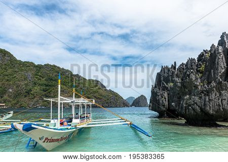 EL NIDO PALAWAN PHILIPPINES - JANUARY 17 2017: Sharp rocks and a boat of island hopping in the El Nido's bay.