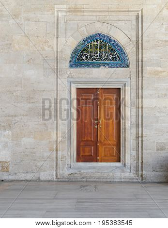 Wooden engraved door on stone wall and tiled marble floor Sulaymaniye Mosque Istanbul Turkey