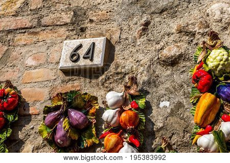 Ceramic number sixty four 64 on a brick wall with plastic onion, garlic and other vegetables