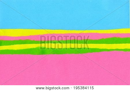 Pink yellow and green strips of paper with the ragged edge on a blue background