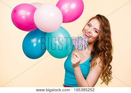 Woman attractive cheerful girl holding colorful balloons and sweet lollipop in hands. Summer holidays celebration and happiness concept. Studio shot bright yellow background