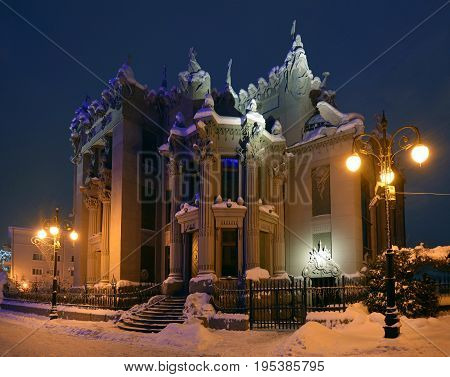Illuminated House with Chimaeras or Horodecki House. Night scene. Building and street are powdered with snow.