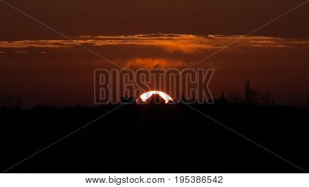 House Of The Falling Sun - Sunset behind distant house silhouette on horizon, burning orange color, flamelike clouds.
