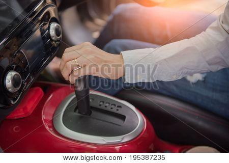 Closeup of hand gear stick driving car.