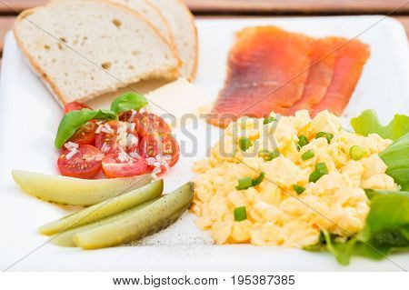 Breakfast set scrambled eggs with chives fish cucumber tomato and bread