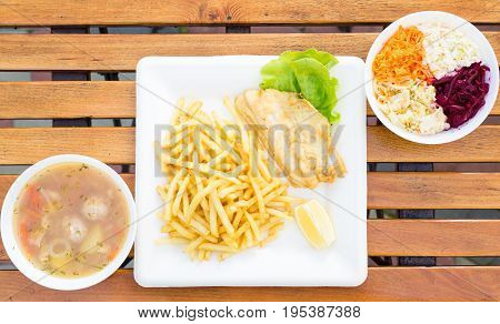 Dinner set fish soup fish and chips and cabbage salad