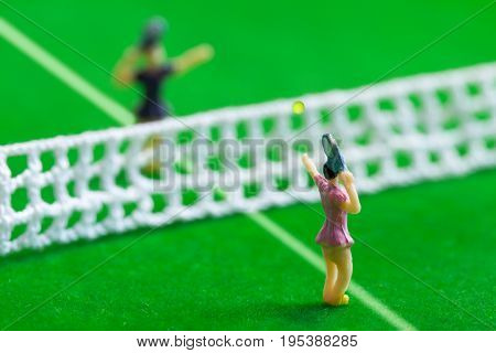 Tennis player figurines playing tennis on grass court