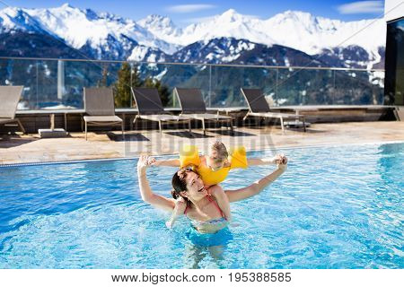 Mother and baby play in outdoor swimming pool of luxury spa alpine resort in Alps mountains Austria. Winter and snow vacation for family with children. Kids in hot tub outdoors with mountain view.