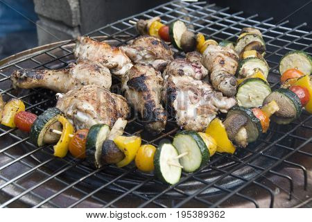 Barbecue chicken and colourful vegetable kebabs of tomato, courgette, peppers and mushrooms cooking outdoors, summer BBQ, UK