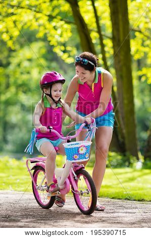 Child riding bike. Kid on bicycle in sunny park. Mother teaching little girl to cycle. Preschooler learning to balance wearing safe helmet. Sport for parents and kids. Family outdoor on bike ride.