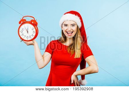 Xmas seasonal clothing christmas time concept. Woman wearing Santa Claus helper costume holding big red clock waiting for celebration