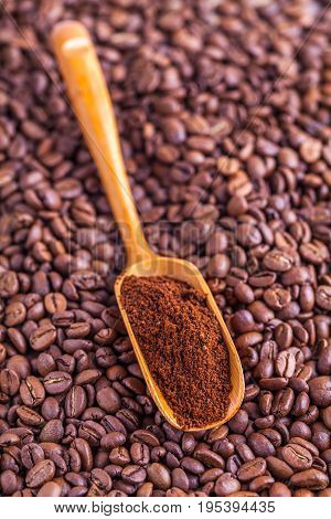 wooden spoon with ground coffee beans background