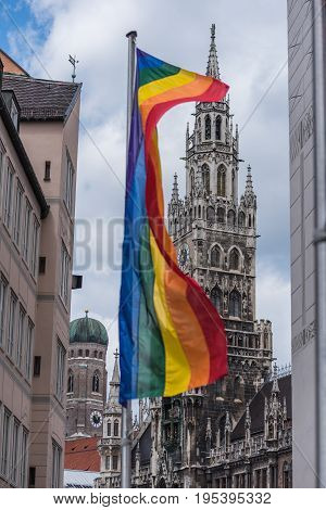 Rainbow flag with Munich town hall and Frauenkirche as background on Christopher Street Day