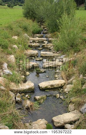Fishing stairs in a riverbed of stone