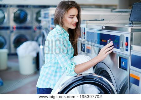 Young Woman Activating Washing Machine