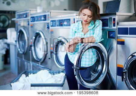 Girl Looking At Watch Near Washing Machines
