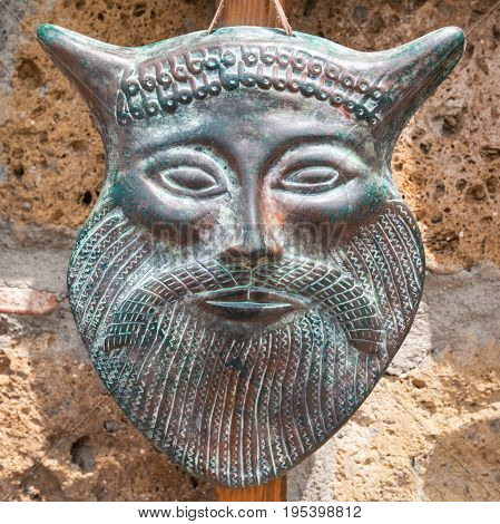 Typical ancient Etruscan mask made of hand-worked bronze.